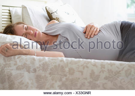 Pregnant woman sleeping in bed - Stock Photo