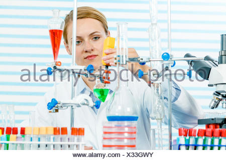 MODEL RELEASED. Female chemist working in laboratory. - Stock Photo