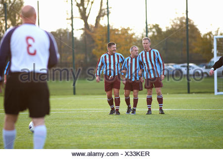 Football players forming wall to defend free kick - Stock Photo