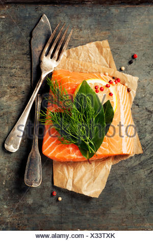 Raw salmon fillet and ingredients for cooking in a rustic style. Top view - Stock Photo