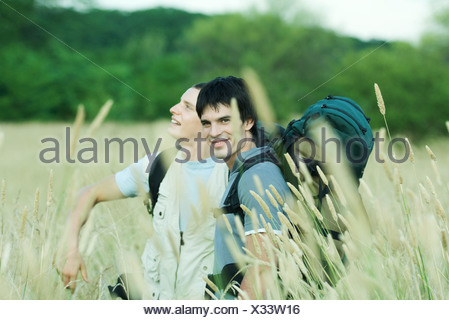 Two hikers standing in field - Stock Photo