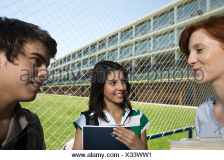 High school friends chatting together outside - Stock Photo
