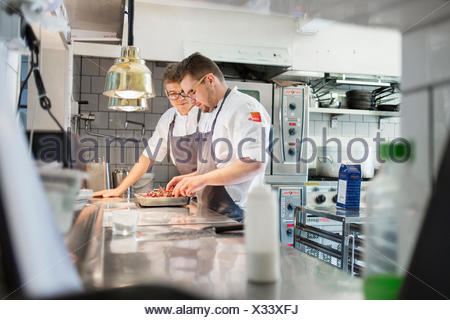 Young chefs with chilies standing together in kitchen - Stock Photo