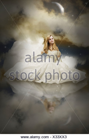 girl sitting in the clouds with the moon behind her - Stock Photo