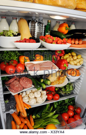 VIEW INSIDE REFRIGERATOR WITH SHELVES FILLED WITH FRESH FOOD - Stock Photo