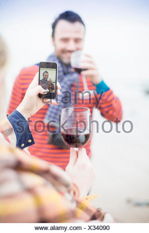 Couple outdoors, drinking wine, woman taking photograph of man - Stock Photo