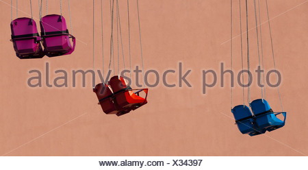 Empty seats of a Chairoplane or swing carousel in front of a house facade, Berlin, Germany, Europe - Stock Photo