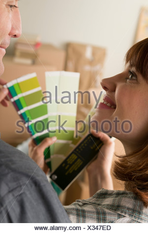 Couple looking at green swatch in new home - Stock Photo