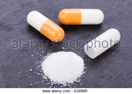 rot orange pillen kapseln medizin drogen wirkstoff detail auf dunklem hintergrund - Stock Photo