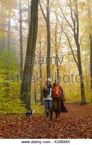 Women walking dog in forest - Stock Photo