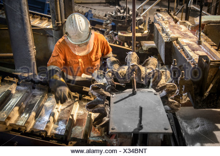 Worker testing metal ingots at aluminum recycling plant - Stock Photo