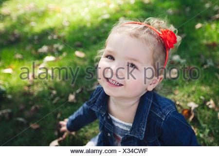 High angle portrait of girl with red hairband wearing denim jacket looking at camera smiling - Stock Photo