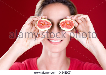 A mid adult woman holding figs up to her eyes - Stock Photo
