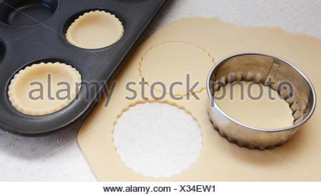 Cutting large circles of pastry to line a bun tin - Stock Photo