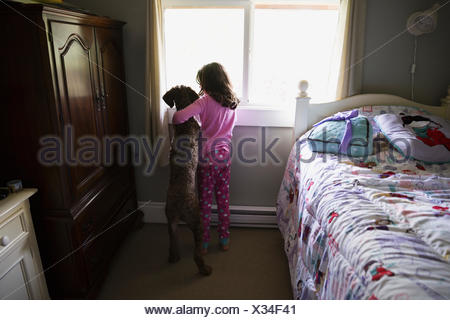 Girl and dog hugging looking out bedroom window - Stock Photo