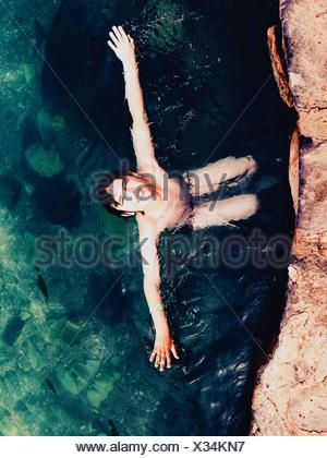 High Angle View Of Shirtless Boy Swimming In Sea - Stock Photo