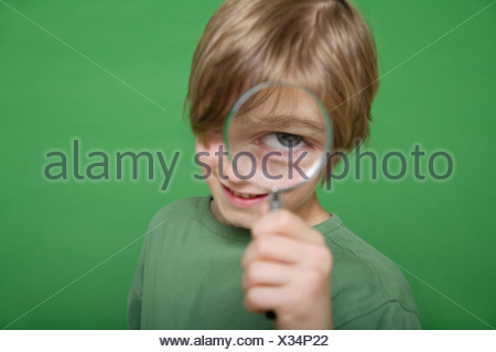 Close up of boy looking through magnifying glass against green background - Stock Photo