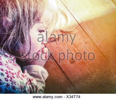 Close-Up Of Cute Young Girl Sleeping On Wooden Surface - Stock Photo