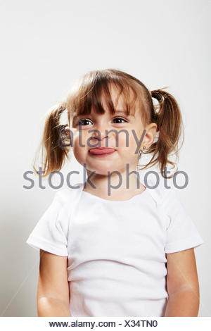 Portrait of young girl with pigtails, making faces - Stock Photo