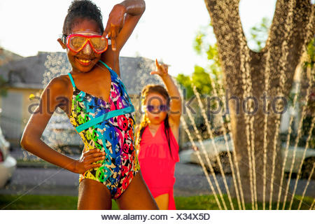 Portrait of two girls posing with arms raised in garden - Stock Photo