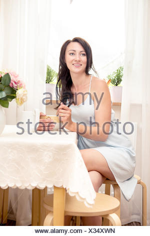 a young woman with a cornflaks cup in the kitchen - Stock Photo