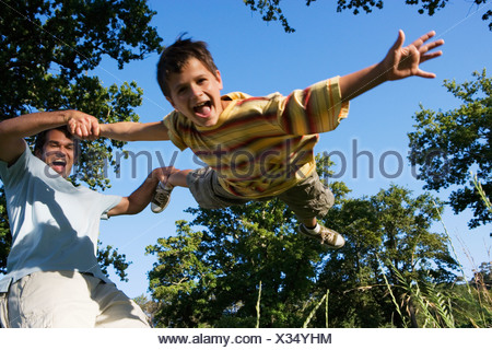Father swinging son 9 11 in woodland clearing boy shouting low angle view tilt - Stock Photo