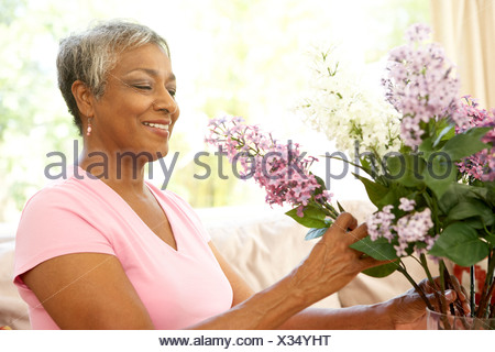 Senior Woman Flower Arranging At Home - Stock Photo