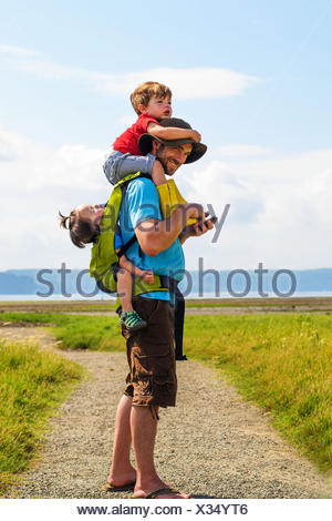 Father carrying son (2-3 ) and daughter ( 2-3) - Stock Photo