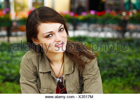 Portrait of smiling woman sitting in park - Stock Photo
