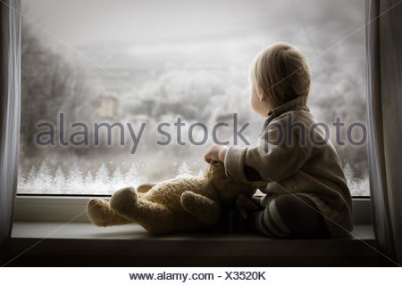 Boy sitting on windowsill with teddy bear and looking at window - Stock Photo