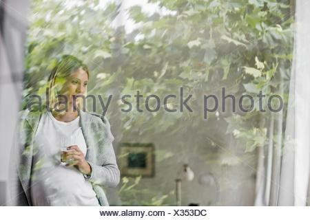 Full term pregnancy young woman at home behind window - Stock Photo