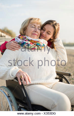 Young woman head to head with her grandmother sitting in wheelchair - Stock Photo