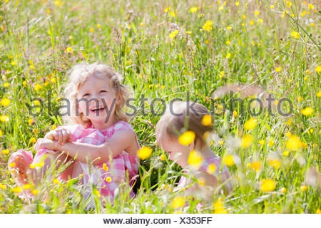 Portrait of smiling baby and young girl sitting in wildflower meadow - Stock Photo
