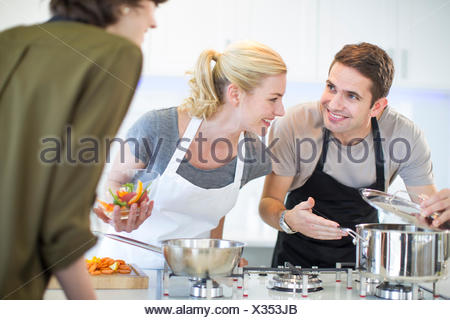Mid adult man and friends preparing food in kitchen - Stock Photo
