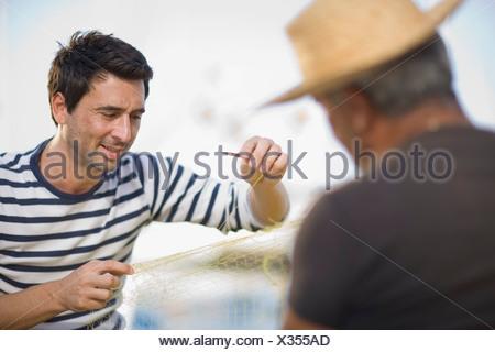 Fisher preparing fishing net - Stock Photo