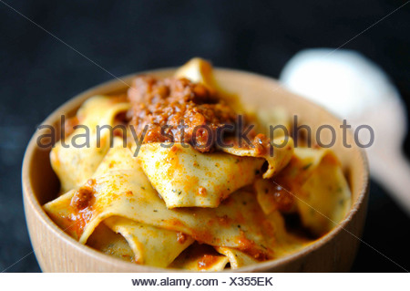 Pappardelle pasta with hare ragout in a wooden bowl