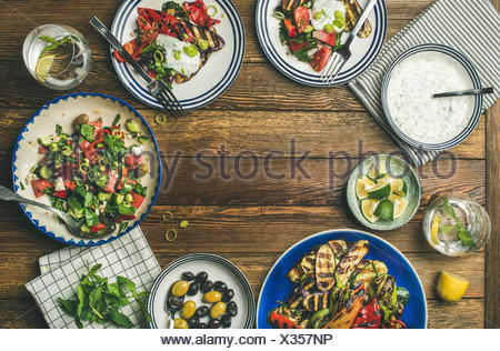 Flat-lay of healthy dinner table setting. Fresh salad, grilled vegetables with yogurt sauce, pickled olives over wooden background, copy space, select - Stock Photo