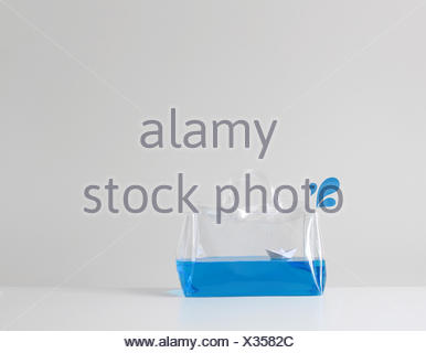 Paper boat floating on blue water in a transparent plastic bag - Stock Photo