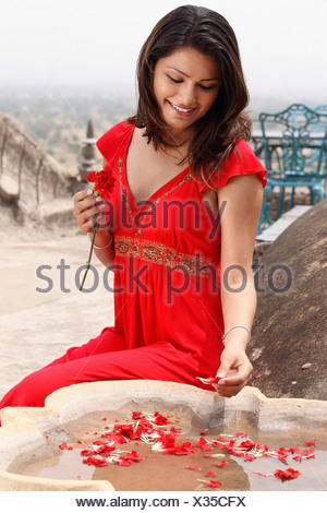 woman putting petals in fountain - Stock Photo