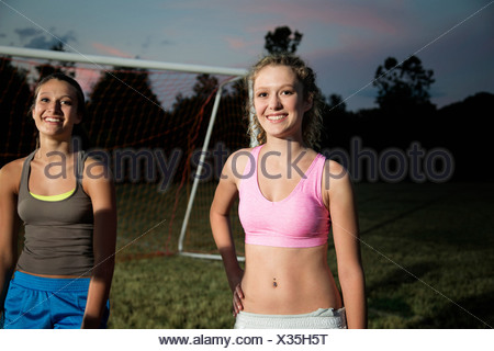 Portrait of two girls on soccer pitch at night - Stock Photo