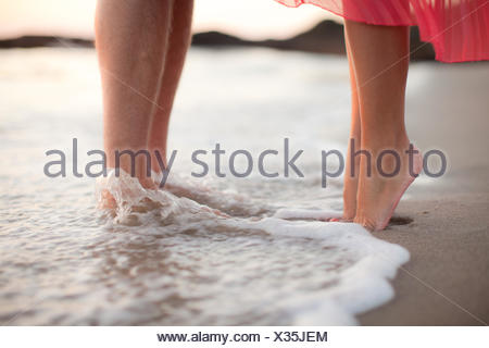 Close-up of a couple standing ankle deep in water on the beach - Stock Photo