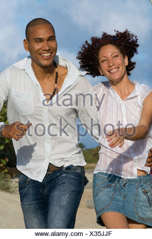 Young multi-ethnic couple walking with arm around each other, Havana, Cuba - Stock Photo
