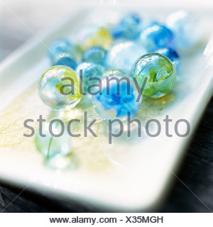 Colourful glass marbles on a dish. - Stock Photo