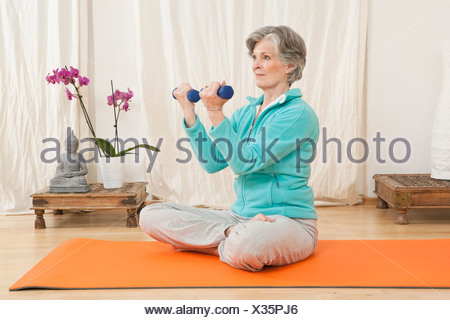 A senior woman working out with hand weights in a yoga studio - Stock Photo