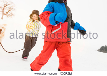 Girl with dog in snow with boy in foreground - Stock Photo