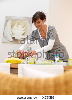 Young woman arranging flowers at breakfast table - Stock Photo