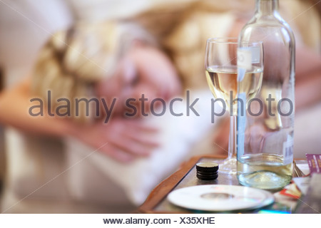 Young woman, asleep on sofa after drinking - Stock Photo