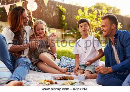Family Enjoying Picnic On Blanket In Garden - Stock Photo