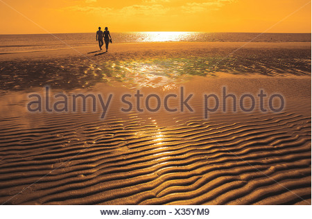 couple walking along the beach at sunset - Stock Photo