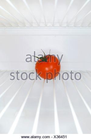 Single tomato sitting on shelf inside refrigerator - Stock Photo
